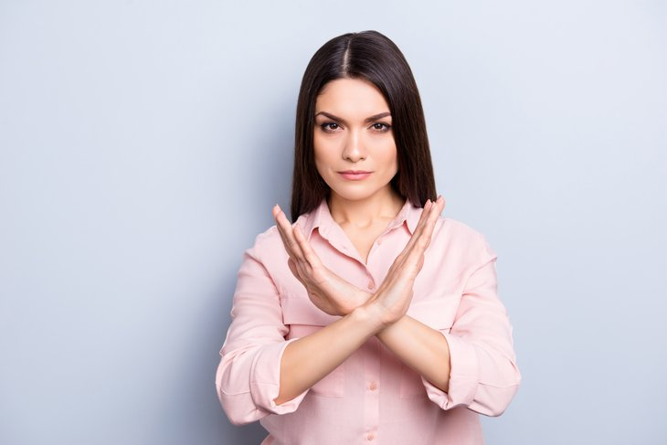 A serious woman gives the timeout hand gesture