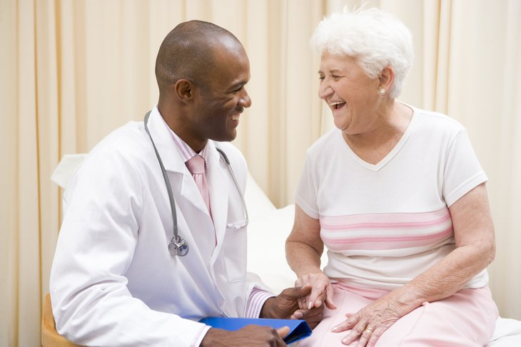 A young black doctor examines a senior patient