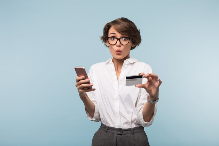 A woman with a smartphone and credit card is taken by surprise