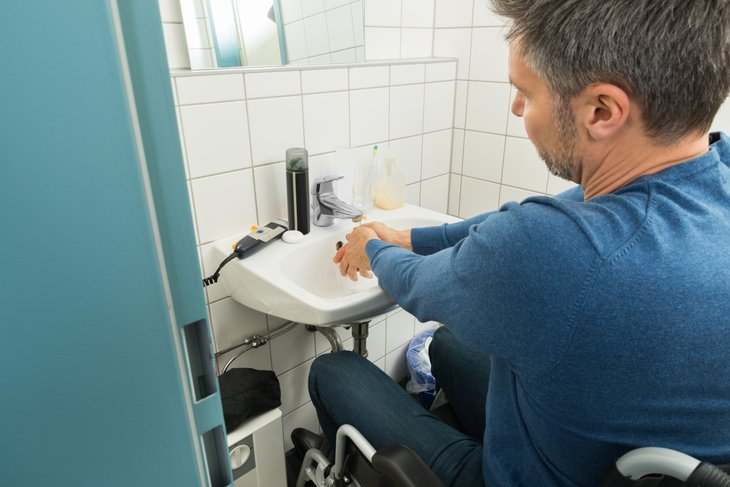 Man Wheelchair accessible bathroom Washing Hands In Bathroom