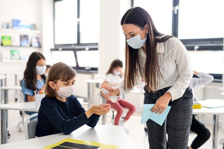 A teacher helps a student with face masks on during the coronavirus crsis