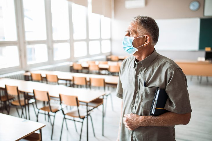 Older teach wearing a face mask in an empty classroom