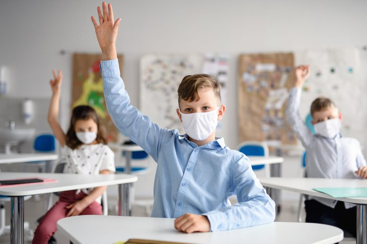 Student in face mask raising hand