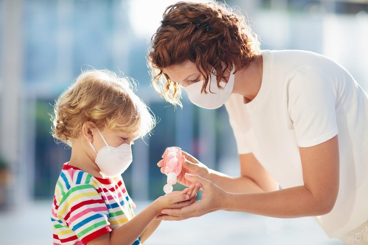 Parent and child use hand sanitizer and face masks at school