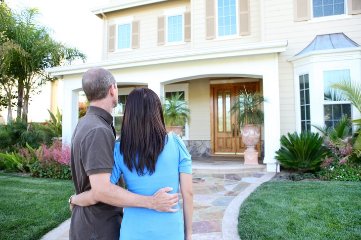 Homebuyers looking at a house with a front porch