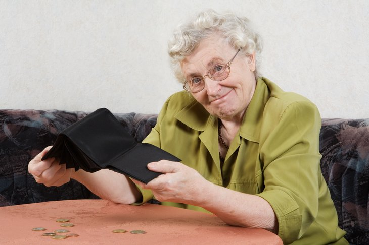 A poor senior woman empties her wallet