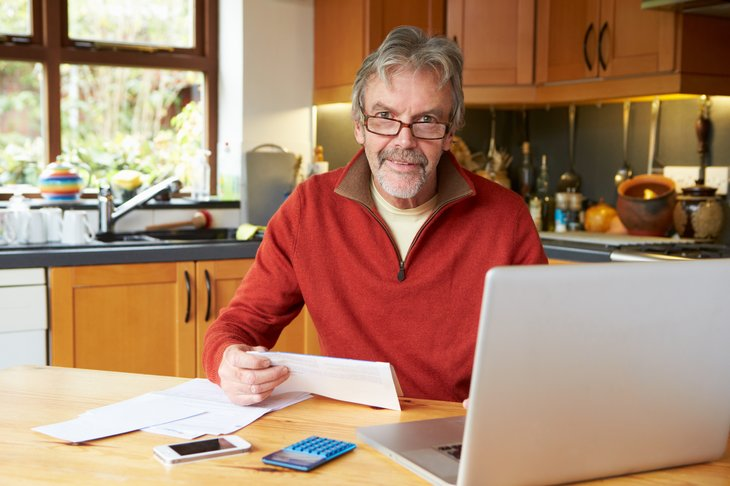 An older man in glasses works on finances at a laptop computer in his kitchen