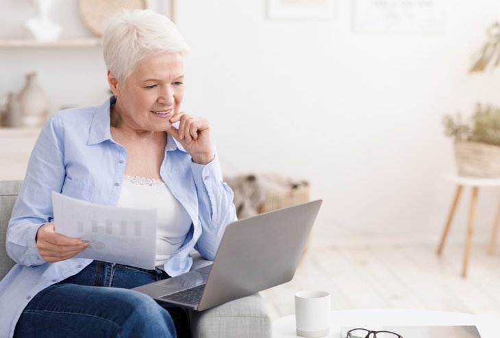 senior woman white gray hair couch crunching numbers computer