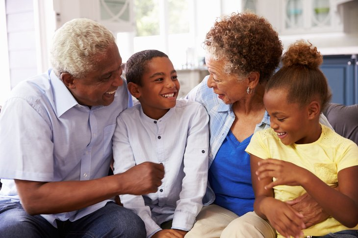 Grandparents spend time with their grandchildren at home on a sofa