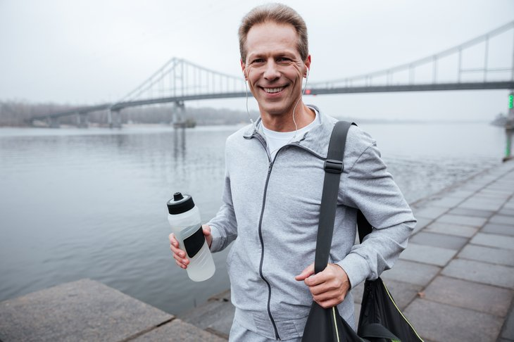 A runner poses with a reusable water bottle and gym bag