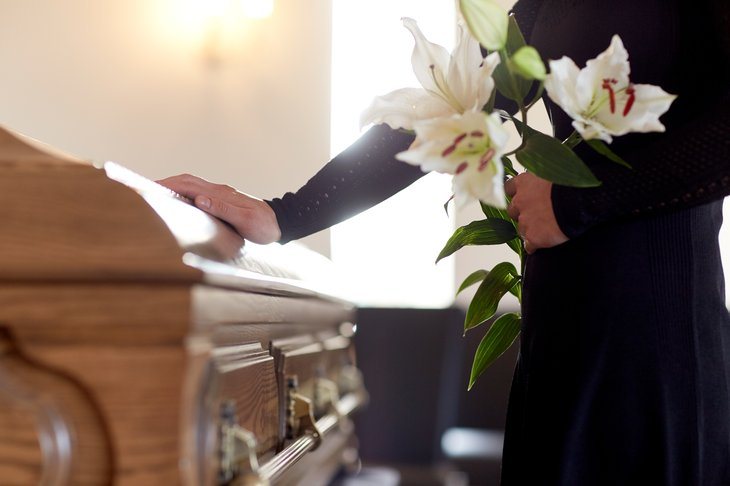Woman touching a casket at a funeral