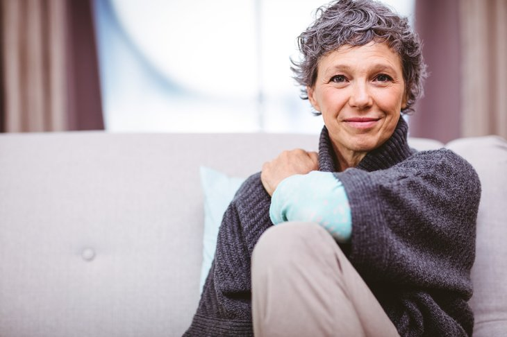 An older woman sitting on her sofa at home