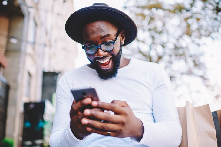 surprised excited dark skinned black african american hipster young man in trendy hat overjoyed