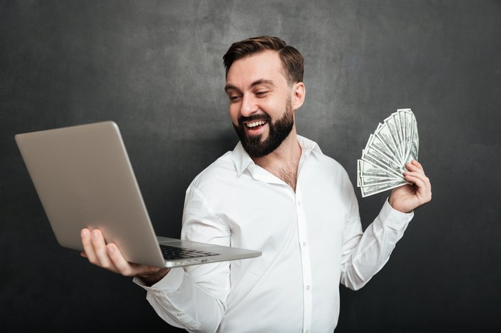 A happy man holds a laptop computer and fan of cash