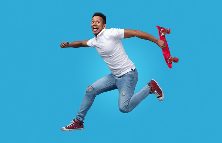 excited young African American man red skateboard jumping blue background
