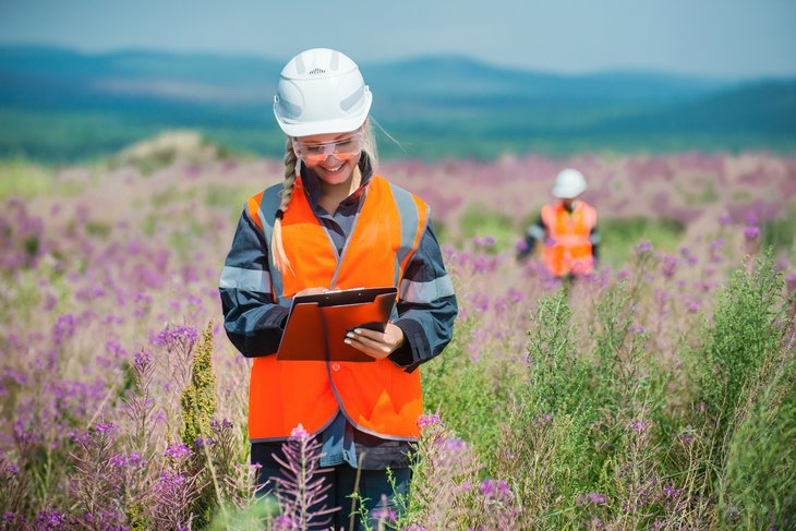 woman scientist hard hat clipboard Researching recultivated field