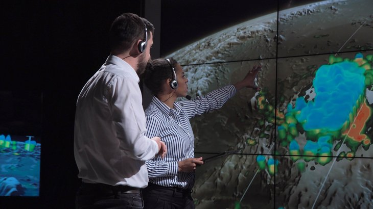two scientists man woman african american white hurricane map and analyzing weather.