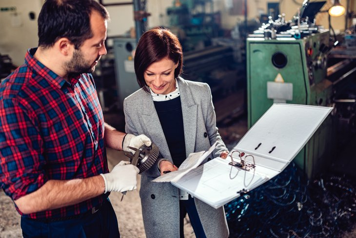 Machinist with woman engineer measuring cogwheel with caliper at industrial manufacturing factory