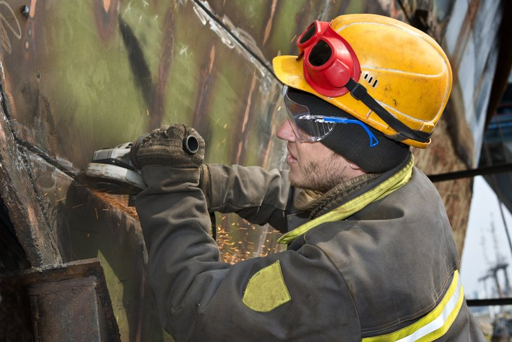 Locksmiths Boilermakers cleans welds on ship's hull