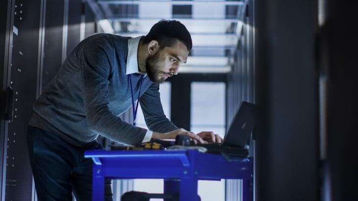 IT Engineer Tool Cart Working Laptop Computer deploying new software Data Center Rack Servers