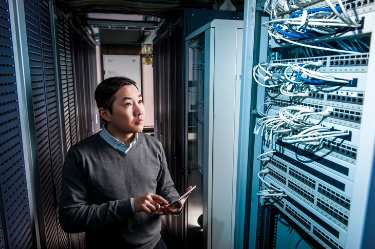 Young asian american engineer businessman in server room