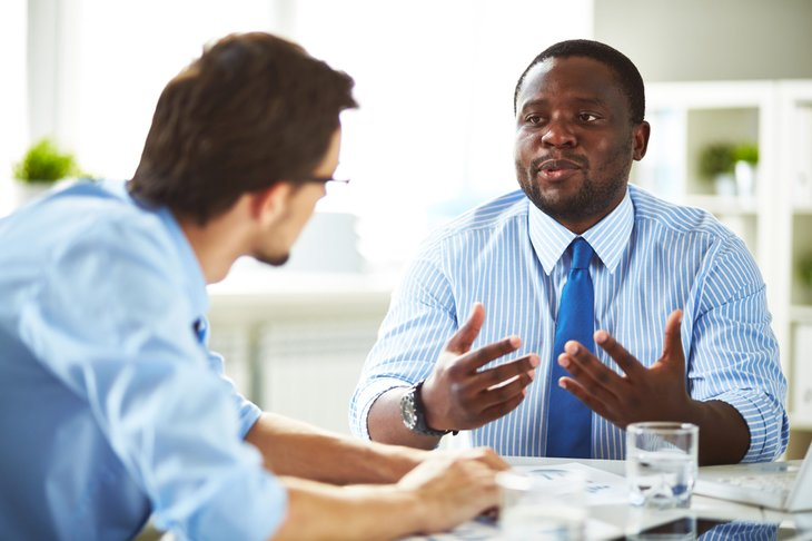 2 men black and white business lawyers work in conversation