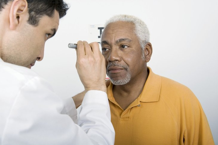 A doctor examines the eyes of an older patient