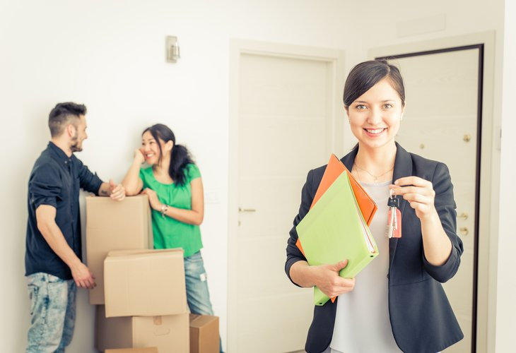 real estate agent woman with clients in new home keys