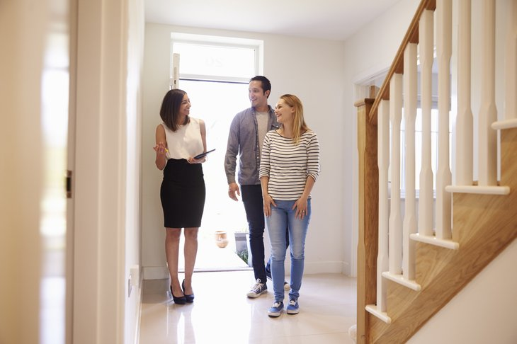 Realtor Showing Young Couple Around Property For Sale