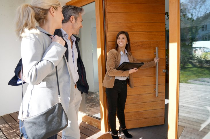 Real estate agent inviting couple to enter house tour