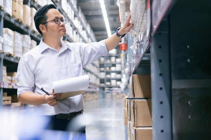 Wholesale, logistic, business, export and people concept - Man warehouse worker checking goods at warehouse