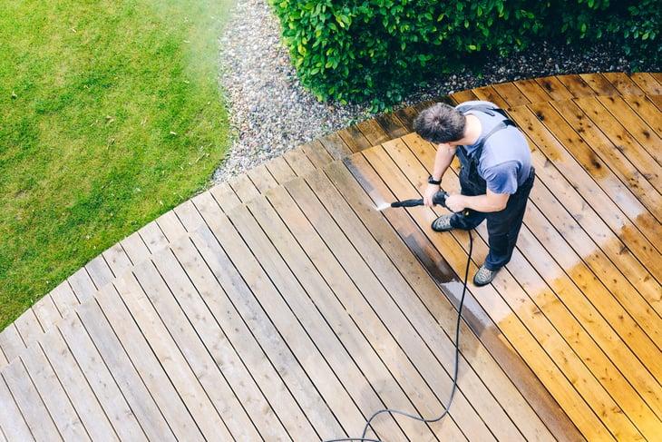 Worker pressure-washing a deck