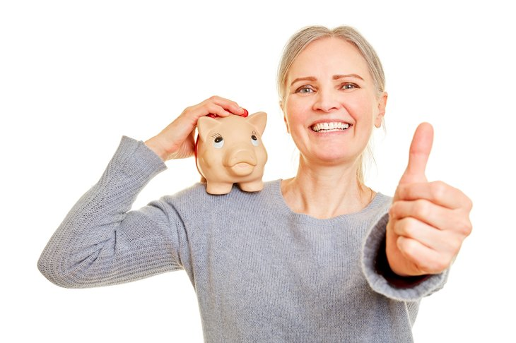 Senior with piggy bank holds her thumbs up