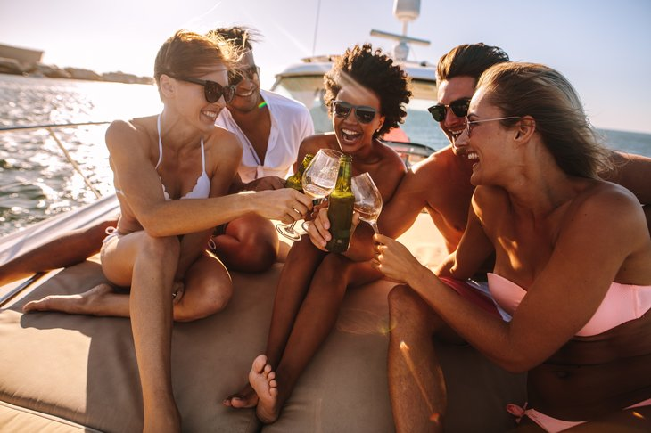 friends having fun on a yacht, drinking wine and laughing. Party on the private boat