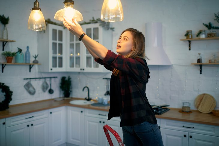 Woman changing light bulbs