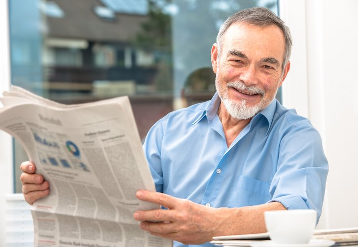Happy retiree reading a newspaper