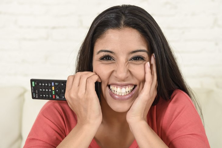 A happy woman smiles and holds a remote control while watching TV