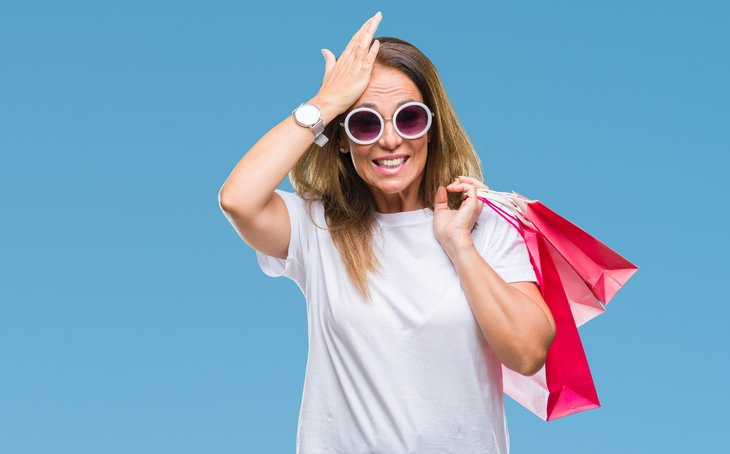 Middle age hispanic woman holding shopping bags head smack regret
