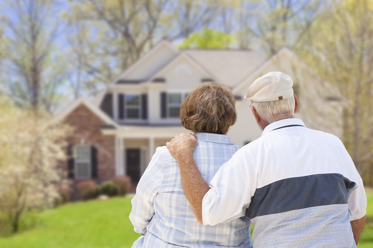 seniors couple man woman backs turned looking at house home