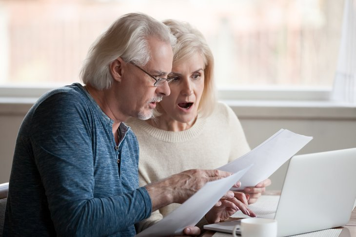 senior man woman worried computer papers