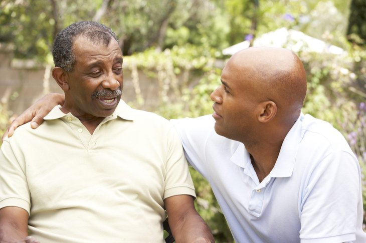 A senior father has a serious conversation with his adult son