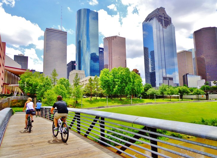 Bicyclists cross wooden bridge Buffalo Bayou Park view downtown Houston