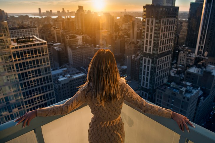 rich. wealthy. woman enjoying the sunset balcony luxury apartments vcity. Luxury