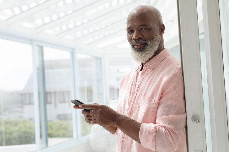A senior black man uses a smartphone