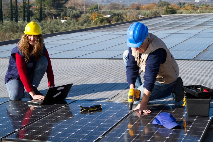 woman engineer man skilled worker install solar panels