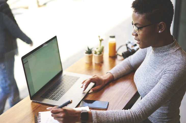 A black woman works remotely on a laptop