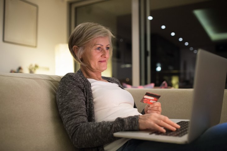 A senior shops online from her living room sofa with a laptop computer and credit card