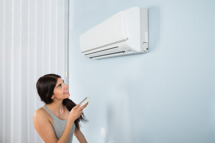 woman adjusting an air conditioner
