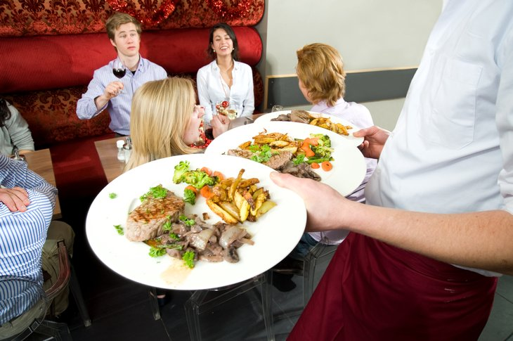 restaurant Waiter carrying plates of food, serving customers crowded