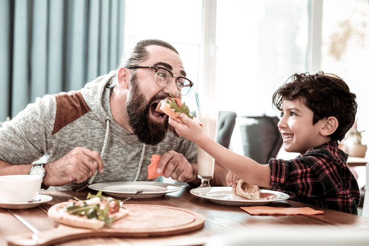 High five. father son eating pizza together